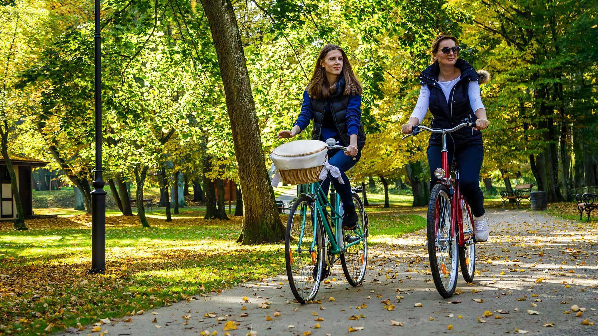Two Women Riding Bicycles In City Park
